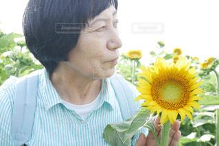 花を抱えている年配の女性の写真・画像素材[2110473]