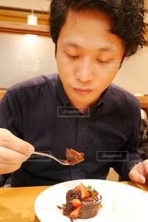食べ物の皿の前のテーブルに座っている少年の写真・画像素材[2265878]