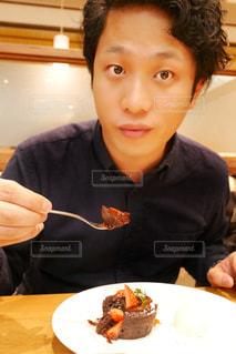 食べ物の皿の前のテーブルに座っている男性の写真・画像素材[2265879]