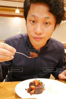 食べ物の皿を持ってテーブルに座っている男性の写真・画像素材[2265882]