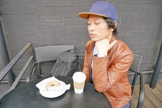 帽子をかぶってテーブルに座っている人の写真・画像素材[2266068]