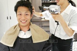 美容室でヘアセット中に、カメラに向かって微笑んでいる男性の写真・画像素材[2270446]
