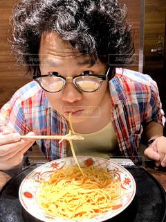 食べ物を食べながらテーブルに座っている女性の写真・画像素材[2382290]