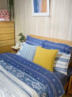 青い毛布が付いているダブルベッドの写真・画像素材[2383559]