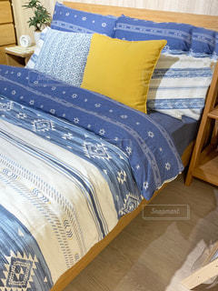 青い毛布が付いているベッドの写真・画像素材[2383580]