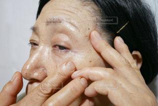 アイクリームを塗る年配の女性の写真・画像素材[2390449]