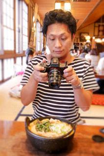食べ物を撮影する男性の写真・画像素材[2488005]