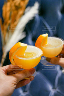 オレンジジュースを一杯持っている人のクローズアップの写真・画像素材[2991181]