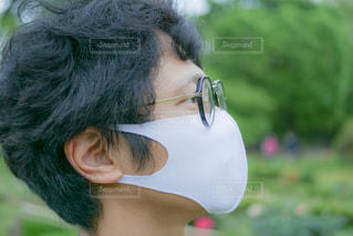 マスクと眼鏡をかけている人のクローズアップの写真・画像素材[3209575]