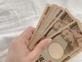 お金を持つ女性の手元の写真・画像素材[3398105]