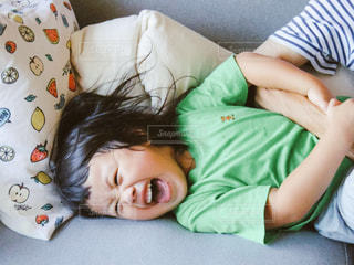 ベッドの上で横になっている少女の写真・画像素材[716461]