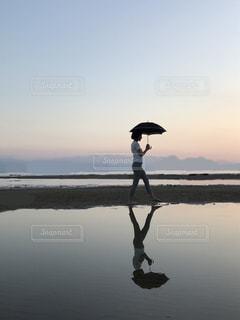水の体の隣に立ちながら傘を持っている人の写真・画像素材[2449146]