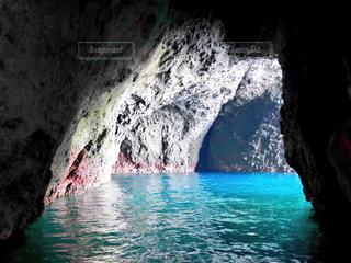 水の体の横にある洞窟の写真・画像素材[1249615]