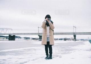 雪の日の河川敷と女性の写真・画像素材[40791]