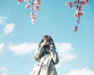 澄んだ青い空の前に立っている人の写真・画像素材[1102947]