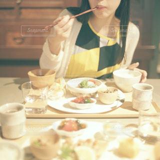 食事のテーブルに座っている女性の写真・画像素材[1237600]