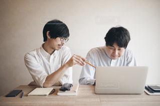 ラップトップを使用してテーブルに座っている人々 のグループの写真・画像素材[1354695]