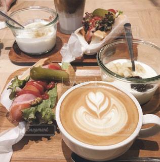 食品やコーヒー テーブルの上のカップのプレートの写真・画像素材[1378440]
