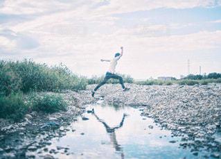 川を飛び越える男性の写真・画像素材[1508954]