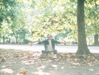 葉っぱで無邪気に遊ぶ男性の写真・画像素材[1535355]