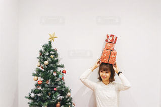 クリスマスツリーと、プレゼントを持つ女性の写真・画像素材[1664022]