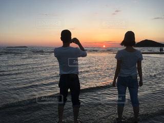 夕日とカップルの写真・画像素材[1499368]