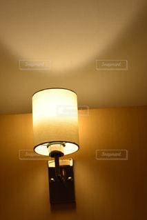 暗い部屋に座っているランプの写真・画像素材[713555]