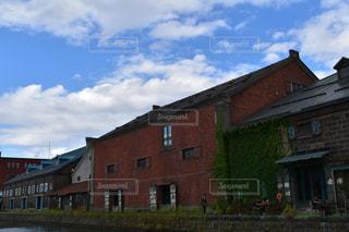 大きなレンガの家の側に時計と建物の写真・画像素材[717082]