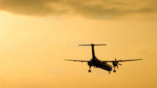 夕焼けの伊丹空港に着陸するプロペラ機の写真・画像素材[856359]