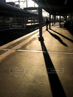 夕暮れのホームで電車を待つ人の写真・画像素材[888368]