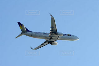 青い空を飛ぶ大型旅客機の写真・画像素材[1556718]