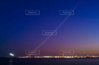 夕暮れの羽田空港を離陸する飛行機の光の軌跡の写真・画像素材[1570932]