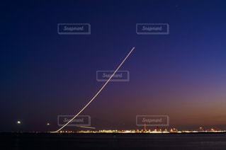夕暮れの羽田空港を離陸する飛行機の光の軌跡の写真・画像素材[1570933]