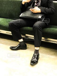 帰りの電車の中でスマホをいじる若者サラリーマンの写真・画像素材[1584851]