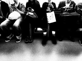 電車の中でみんなそろってスマホをいじる人たち。の写真・画像素材[1604697]