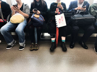電車の中でスマホをいじるたくさんの人たちの写真・画像素材[1604698]