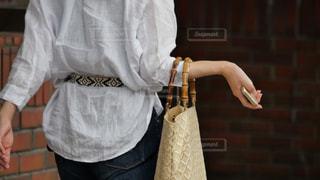 右手にスマホを持ち歩く大人の女性の後ろ姿の写真・画像素材[2241882]