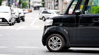 交差点で対向車線の車を待つ黒い自動車の写真・画像素材[2241918]