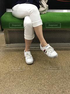 京阪電車の車内で脚を組んでいる大人の女性の写真・画像素材[2252045]