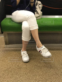 京阪電車の車内で脚を組んでいる大人の女性の写真・画像素材[2252046]