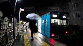 雨の夜の和田岬駅で発車を待つ電車に乗り込むサラリーマンの写真・画像素材[2301280]
