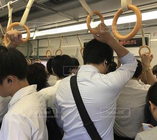 朝の通勤電車に揺られる疲れたサラリーマンの後ろ姿の写真・画像素材[2415896]