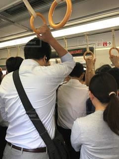 朝の通勤電車に揺られる疲れたサラリーマンの後ろ姿の写真・画像素材[2415897]
