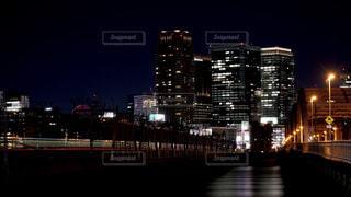 グランフロント大阪の夜景をバックに淀川を渡る阪急電車の光の軌跡の写真・画像素材[2515334]