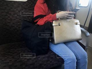 通勤電車の中でスマートフォンを操作する大人の女性の写真・画像素材[2604532]