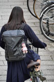 駐輪場から自転車を出して乗ろうとする制服姿の女子高生の写真・画像素材[2637531]