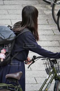 駐輪場から自転車を出して乗ろうとする女子高生の写真・画像素材[2637532]