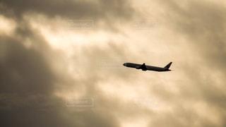 夕暮れの中、高度を上げる旅客機の写真・画像素材[2745845]