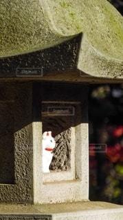 東京世田谷の豪徳寺境内にある石灯籠で日向ぼっこをする招き猫の写真・画像素材[2783828]