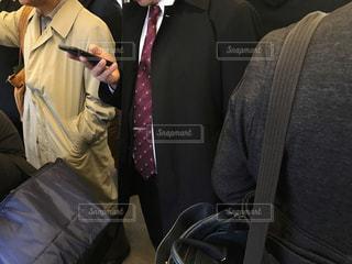 スーツとネクタイ姿のサラリーマンが電車の中で片手でスマホを操作しているシーンの写真・画像素材[2797671]